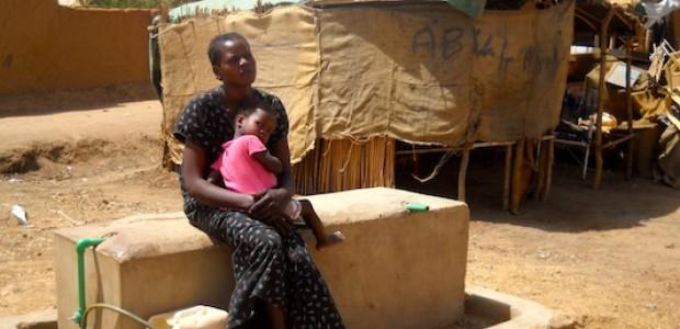 أم مع طفلها في أحد معسكرات الحاج يوسف، تنتظر في معاناة قاسية ترحيلها الى جنوب السودان.