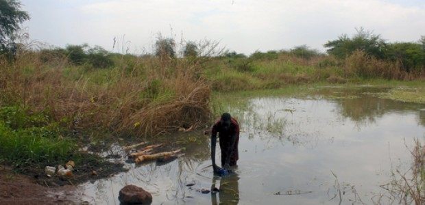 A woman in Rubkona County, Unity State, South Sudan fetching water for domestic use from a stream just a few meters away from the Unity oil field, November 4, 2013.