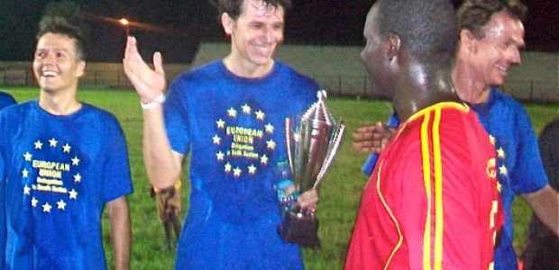 A player of the EU team poses with the trophy while shaking hands with one of the coaches' players, May 11.