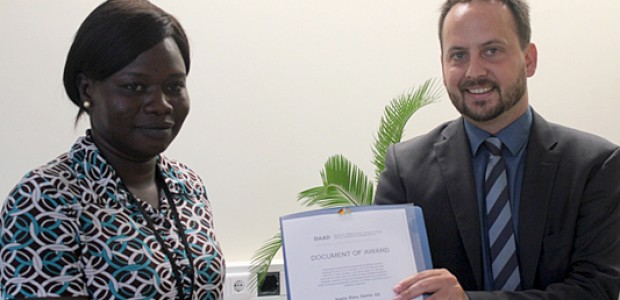 The German Deputy Ambassador Johannes Sperrfechter hands over a DAAD scholarship award to Santa Jima in Juba, Aug. 7.