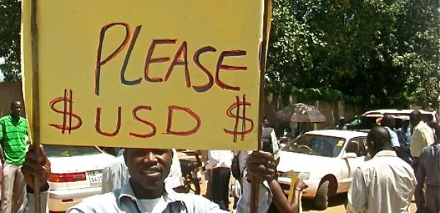 موظف في الأمم المتحدة يحمل لافتة تطالب بالدفع بالدولار بدلا من الجنيه جنوب السوداني في جوبا، 13 أغسطس، 2012.