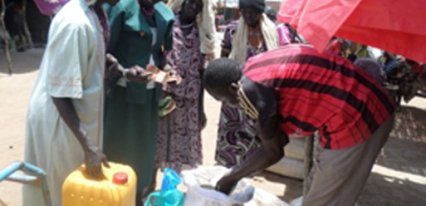 Adut Ring trying to sell a plastic water container in Kuajok, April 2015.