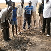 A group of civilians gathers around a cluster bomb crater caused by a Sudan Armed Forces attack last year, April 11, 2012.