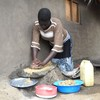 Araka grinds groundnuts on a stone in order to fix a meal for 15 people every day