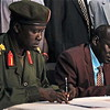 The SPLA representative Brig. Gen. Michael Majur (left) and the representative of George Athor, Abraham Thon (right) sign the ceasefire agreement.