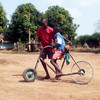 Children in South Sudan's Yei town, Central Equatoria State, play with their self-made bicycle, April 12, 2015. (photo: The Niles | Ochan Hannington)