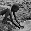 A boy drinks from a stagnant water source in Kuajok, South Sudan, April 21, 2012. (photo: The Niles | Aping Kuluel)