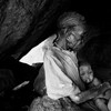 An old woman with a toddler, hiding in a cave in the Nuba Mountains.