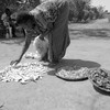 A woman in Northern Uganda dries vegetables in the sun.