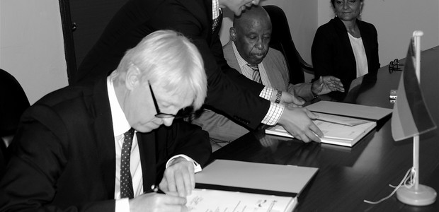 German Ambassador Johannes Lehne (left) and the JMEC Chairman, Festus Mogae signing the Funding Agreement in Juba, June 23, 2016.                        (photo: The Niles | Akim Mugisa)