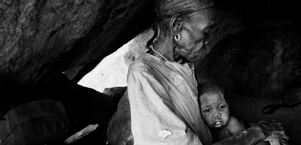 An old woman with a toddler, hiding in a cave in the Nuba Mountains. (photo: The Niles | Marc Hofer)