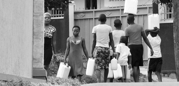 Women and children carrying jerry cans filled with water. (photo: The Niles | Henry Lutaaya)