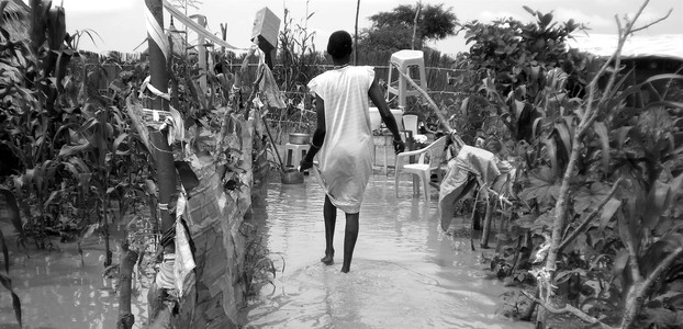 A woman saves her belongings as her homestead drowns in floods, Unity State, August 9, 2013. (photo: The Niles | Bonifacio Taban)