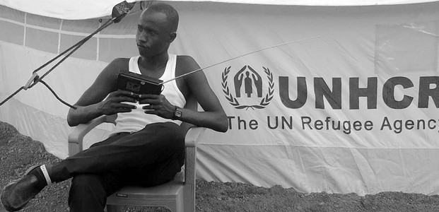 A South Sudanese seeking refuge in Northern Uganda listens to the radio. (photo: The Niles | Ochan Hannington)